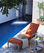 Lounger on summery terrace next to swimming pool with waterfall