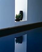 Two black vases in niche above swimming pool