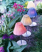 Tealights with lampshades in various colours decorating summer garden