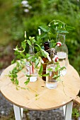 Arrangement of bindweed in swingtop bottles on small wooden table outdoors