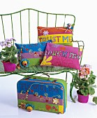 Colourful cushions and hippy-style suitcase on and around metal bench