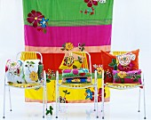 Colourful cushions on three chairs in front of striped cloth