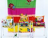 Bunte Kissen auf drei Stühlen vor gestreiftem Tuch
