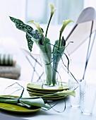 Tischdeko in Grüntönen mit in Servietten gewickelten Kallas