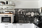 Kitchen utensils hung from rod on ornate, black-and-white, tiled splashback and oven below open shelves