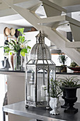 Oriental lantern and houseplants on console table under staircase