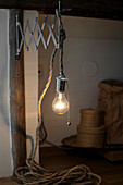 Light bulb hanging from chunky cord on vintage extending wall-bracket