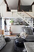 Offener Wohnraum mit grauer Polstergarnitur, im Hintergrund Treppe und Küche