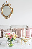 Spherical vase of roses and candelabra on coffee table and gilt-framed mirror above sofa with scatter cushions in background