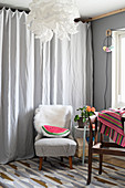 Watermelon-slice cushion on retro armchair in front of grey curtain