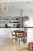 Gedeckter Esstisch mit verschiedenen Stühlen in großer, offener Küche