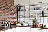 Open shelving, wooden worksurface and brick wall in white kitchen