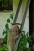 Old sharpening stone leaning against house façade in garden