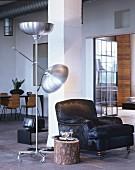 Schwarzer Sessel und Baumstamm als Beistelltisch im Industrieloft