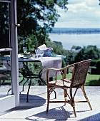 Korbstuhl und runder Tisch auf der Terrasse mit Blick auf den See