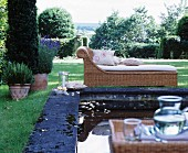 Wicker chaise longue next to pool in classic summer garden
