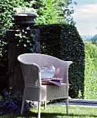 Stacked crockery on wicker chair in classic summer garden