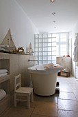 Free-standing bathtub in cream bathroom
