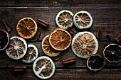 Verschiedene Trockenfrüchtescheiben mit Zimtstangen auf Holzuntergrund