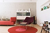 Retromöbel und Vasensammlung im Wohnzimmer mit Betonwand