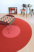Stool on round rug next to three small retro tables