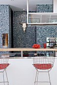 Designer chairs at kitchen counter and speckled wall