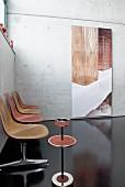 Retrobank und moderne Kunst vor einer Betonwand