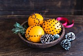 Orange and clove pomanders in wooden bowl (festive)