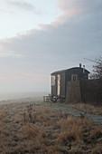 Builder's trailer in wild, misty meadow at twilight
