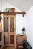 Sliding door made from reclaimed wood in tiny house with wood-panelled walls