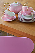 Pink tea service stacked on wooden table