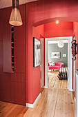 Red fitted cupboards in hallway with red walls and view into bedroom