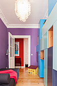 Modular cabinets in shades of blue in guest room with purple wall