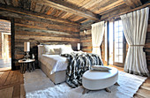 Bed on white fur rug in rustic bedroom