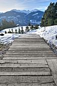 Weg aus alten Holzbohlen im Schnee mit Blick auf die Berge