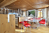 Transparent, modern dining set with red cushions in front of open-plan kitchen