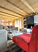 Moderne Möbel im Wohnzimmer mit Holzdecke und offenem Kamin
