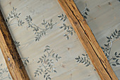 Wooden ceiling painted with pattern of leaves between beams