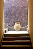 Old terracotta pot on landing against purple wall