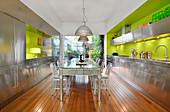 Verspiegelter Tisch in der Küche mit Edelstahlfronten und grüner Wand
