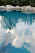 Blue sky and clouds reflected in swimming pool wtih stone edging