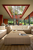 Polyrattan furniture in outdoor lounge on roofed terrace with trees growing through opening in roof