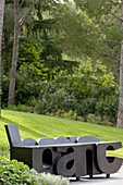 Artistic bench made from large black letters in garden