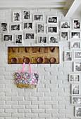 Gerahmte, schwarz-weisse Familienfotos und Garderobe an weiss gestrichener Ziegelwand