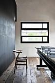 Klassikerstuhl und langer Tisch auf restauriertem Dielenboden vor Kippfenster