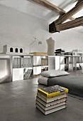 Matratze und Bücherstapel auf Betonboden vor offenem, weißem Regal mit Stehordnern