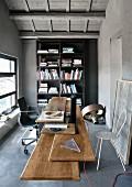 Schreibtisch mit verschiedenen Upcycling-Tischplatten vor schwarzem Bücherregal in Büro