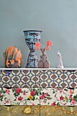 Collection of ornaments on top of chest of drawers with drawers covered in various patterns