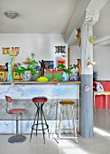 Breakfast bar, column and colourful eclectic furnishings in loft apartment