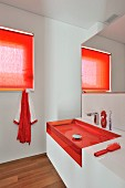 Transparent sink and red accents in modern bathroom